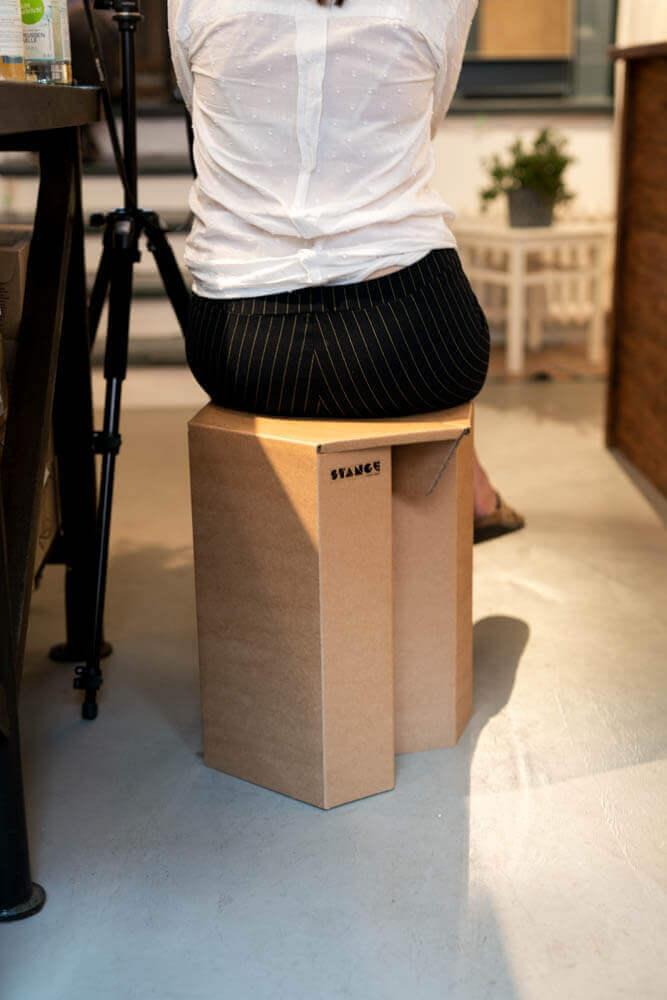 Teilnehmerin auf nachhaltigem Papphocker von STANGE Pappmöbel