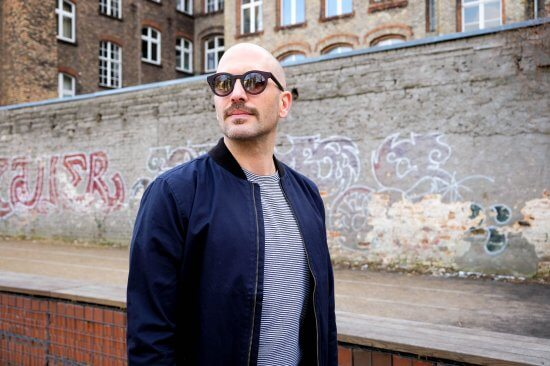 Moody trägt vor einer Kreuzberger Hauswand eine GOBI Amsterdam Sonnenbrille zu T-Shirt und Blouson